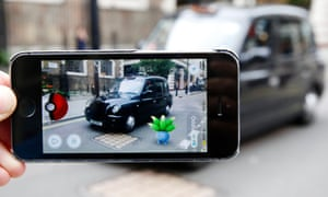 An oddish Pokemon character appears in front of a London taxi during a game of Pokemon Go