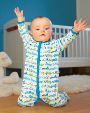 Toddler playing on floor wearing babygro with cars on it