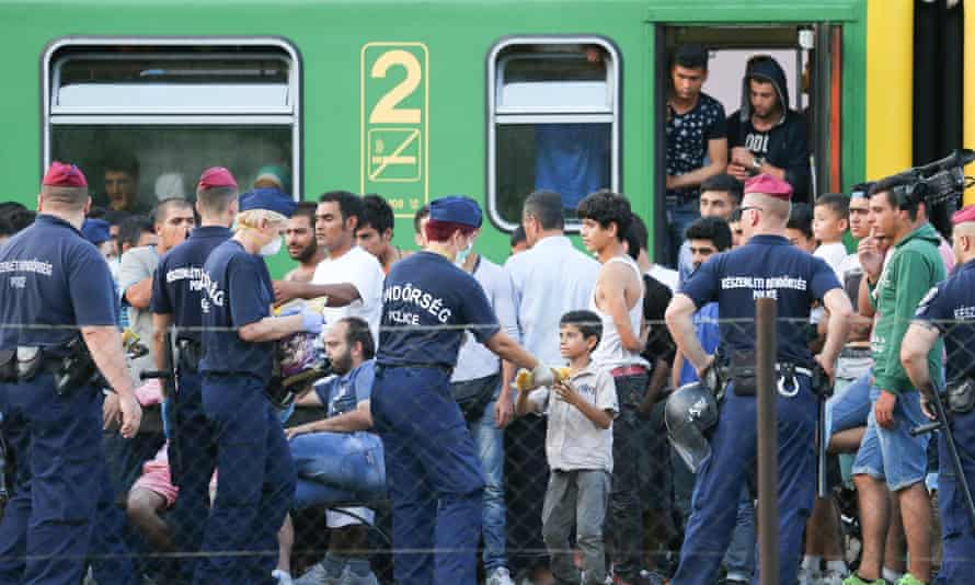 Police escort people off a packed train in Hungary and march them to a nearby camp