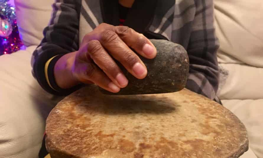 A woman holds a stone used for breast-ironing.