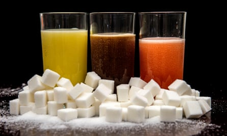 Carbonated drinks surrounded by cubes of sugar