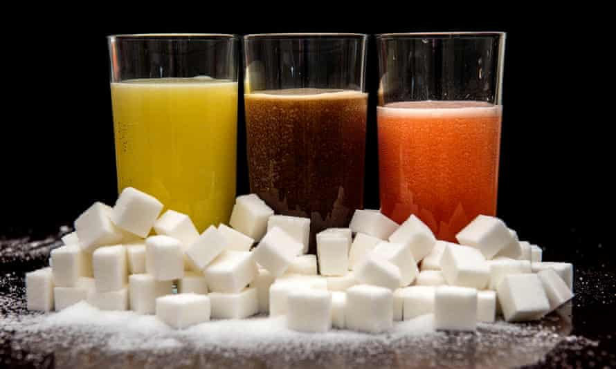 A variety of fizzy drinks with a mound of sugar cubes