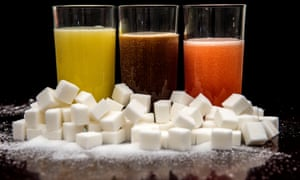 Juice drinks and sugar lumps in foreground