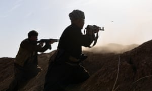 Kurdish peshmerga fighters fire at an Isis position near Mosul