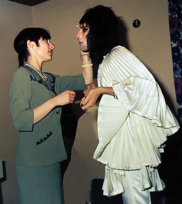 Freddie Mercury wearing a Zandra Rhodes creation with a makeup artist before going on stage at a London concert in 1974.