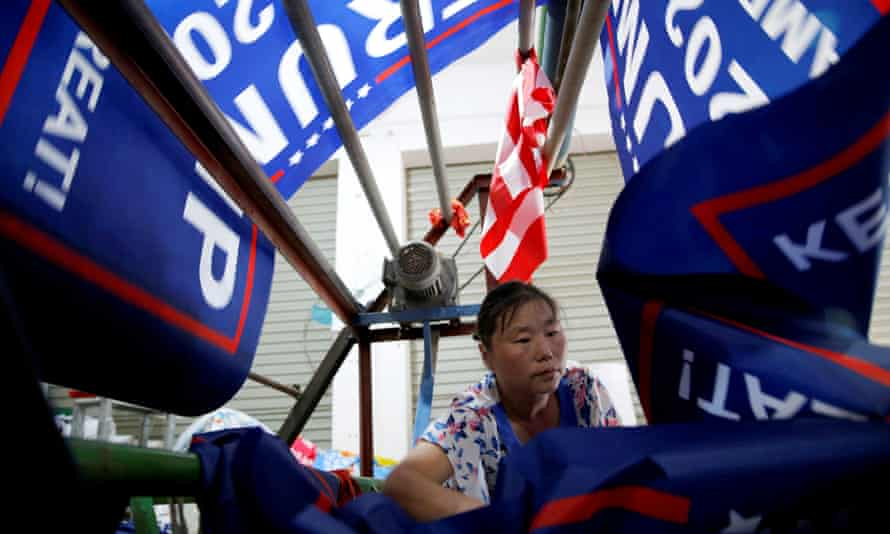 """A worker at Jiahao flag factory in China makes flags for Donald Trump's """"Keep America Great!"""" 2020 re-election campaign."""
