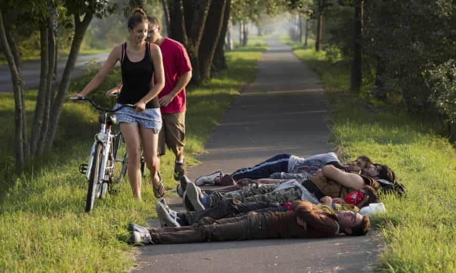 Local cyclists pass a group of Afghan men who crossed from nearby Serbia sleeping on a bicycle path in Morahalom, Hungary.