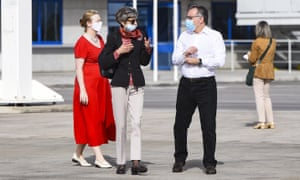The UK ambassador to Greece, Kate Smith (C), and Greece's alternate minister of immigration policy, Giorgos Koumoutsakos, await the refugees at Athens international airport
