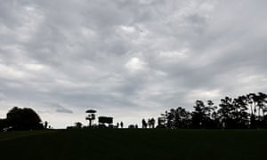 Patrons head off the course after the severe weather warning horn suspended play.