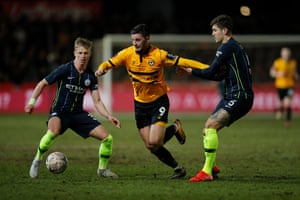Newport County's Padraig Amond (centre) battles for the ball with Manchester City's Oleksandr Zinchenko (left) and Manchester City's John Stones.