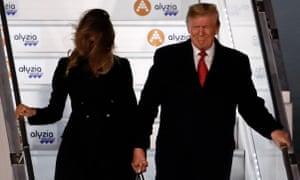 A windswept Melania and Donald Trump disembarking a plane.