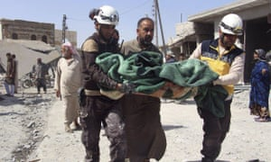 Syrian civil defence workers carry a victim after an airstrike hit a market killing several people in the village of Ras el-Ain.