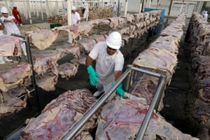 A worker spreads salted meat which will be dried and packed at a JBS plant in Santana de Parnaiba, Brazil, 19 December 2017.