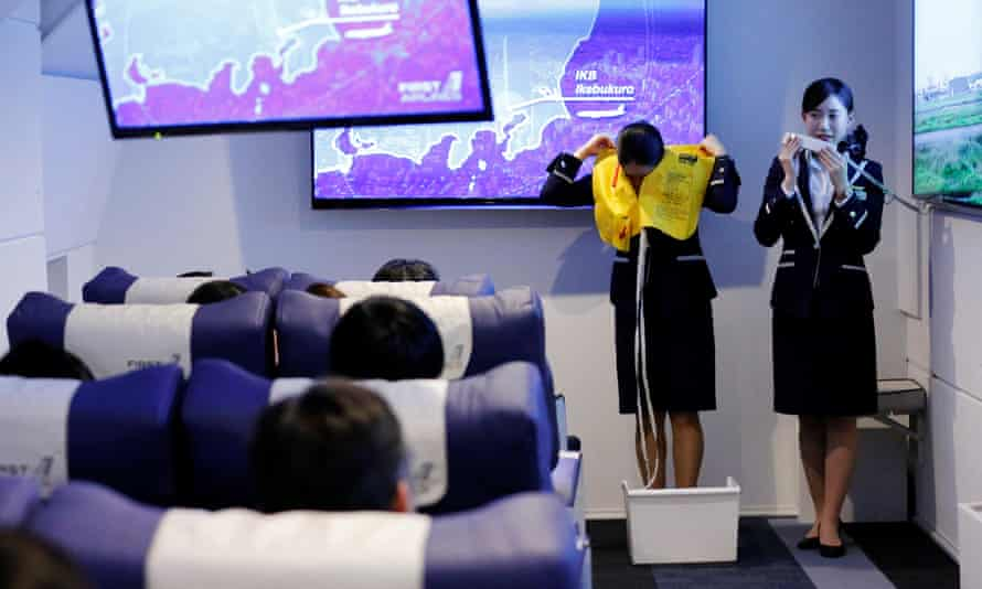 Staff dressed as flight attendants perform a safety demonstration.