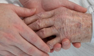 A nurse holds the hand of an elderly patient. Older people get trapped in hospital in areas where social care is inadequate.