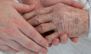 A nurse holds the hand of an elderly patient