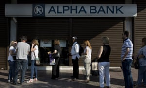 People queue to use an Alpha Bank cashpoint in Athens.