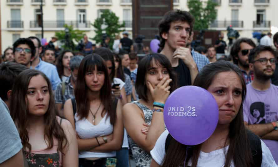 Podemos supporters in Madrid watch the announcement of the first results from Sunday's Spanish election.