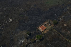 An aerial view shows a house surrounded by burnt vegetation.