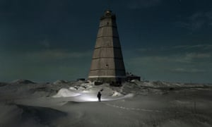 Slava walks to the old lighthouse near Khodovarikha meteorological station in the Russian Arctic.