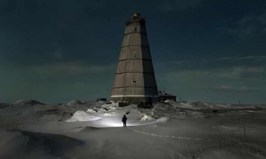Slava walks to the old lighthouse near Khodovarikha meteorological station in the Russian Arctic.