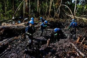 Workers from Argentine firm Pluspetrol clean up after an oil spill in the Amazon region of Loreto, 10 August 2011, after about 1,100 barrels of oil were leaked into the jungle