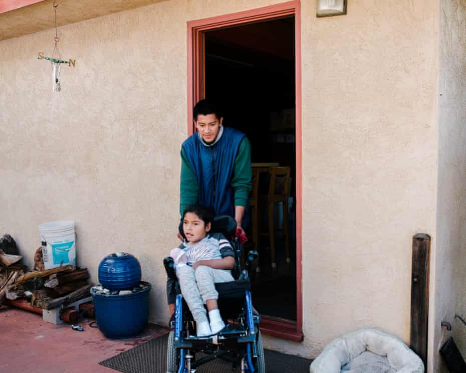 Juan Antonio wheels his daughter Lesly into the backyard of their host's home so they can eat in the garden together.