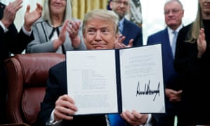Donald Trump participates in a signing ceremony for the directive.