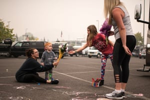 Rebecca Manley and her son, James, accept a bouquet from volunteers handing out flowers at an evacuation site in the parking lot of the Clackamas Town Center on 11 September 2020.