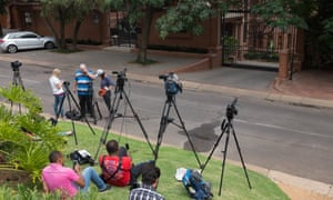Journalists wait outside the home of Oscar Pistorius's uncle in Waterkloof, Pretoria, after the court ruling.