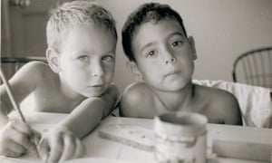 Two young boys side by side, one blond with his arms stretched on the table, one dark, both looking at the camera
