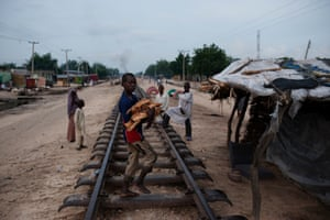 A child in the displaced people settlement next to the railway line in West End, Maiduguri, carrying firewood for cooking purposes.