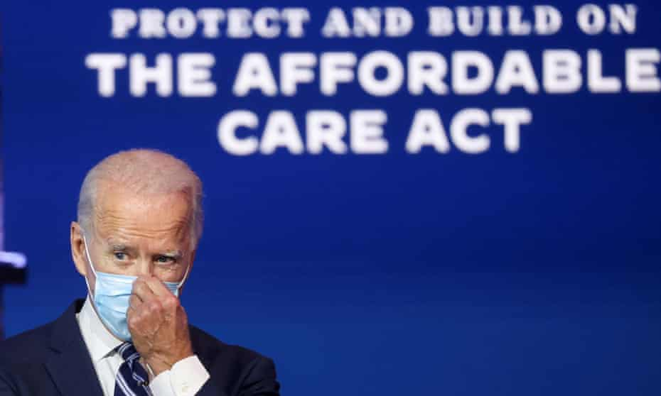 Joe Biden adjusts his mask during a discussion of healthcare and the Affordable Care Act in Wilmington, Delaware last November.