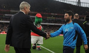 Arsène Wenger shakes hands with Danny Cowley, watched by Gunnersaurus, before Lincoln's FA Cup quarter-final at Arsenal in March 2017