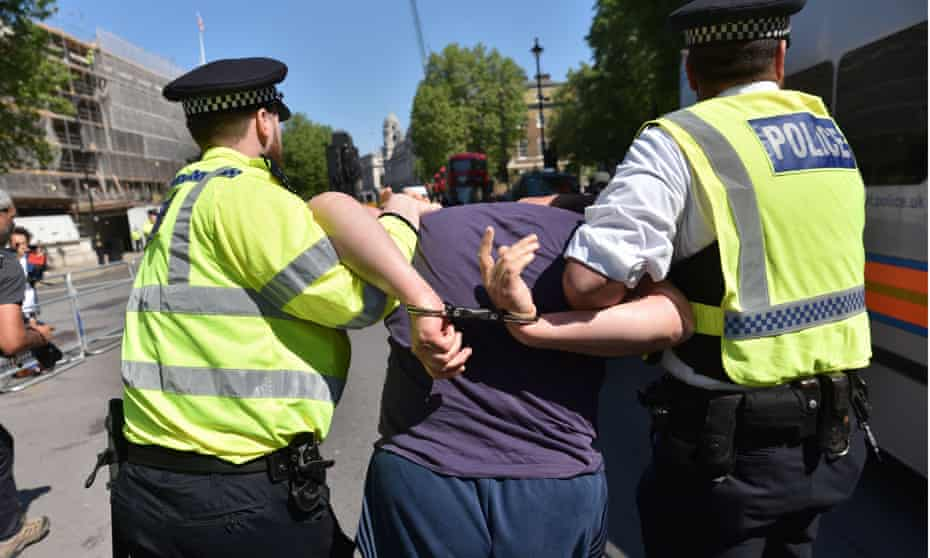 Two police officers lead a handcuffed man towards a police van