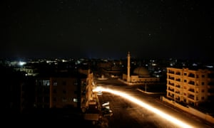 A vehicle drives past a mosque at night in Idlib.