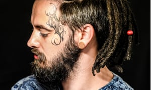 Bearded man with large tatoo down the side of his face