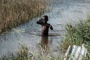 A boy wades through floodwater from cyclone Idai in Beira