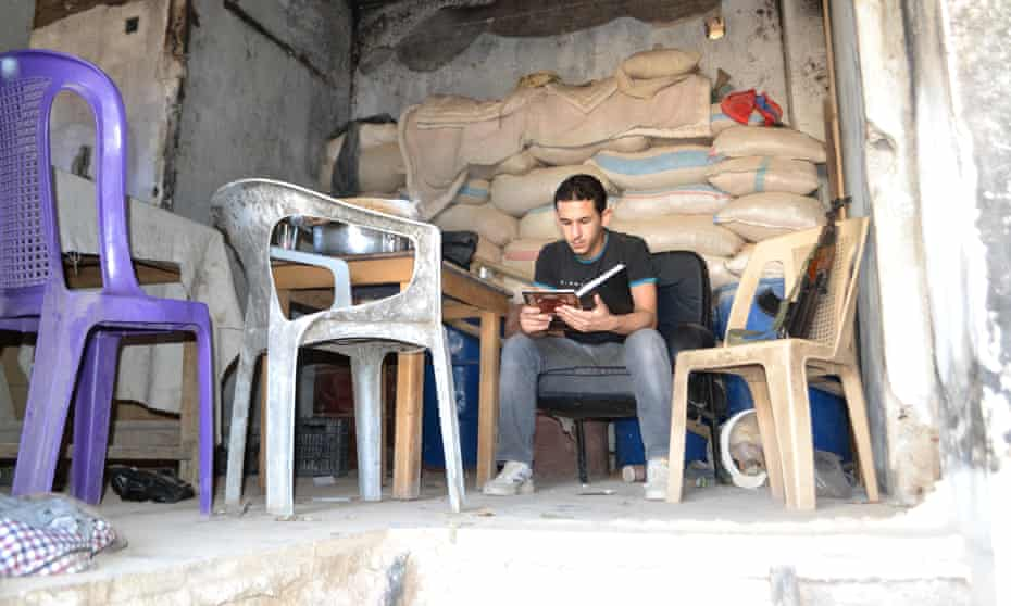 An anti-Assad fighter reading on the frontline