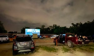 People enjoy a movie from their cars, separated from other cars by a 10ft orange fencing in an effort to respect social distancing at the Ocala drive-in theatre in Ocala, Florida, at the weekend.