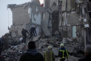Emergency personnel searching through rubble of damaged building