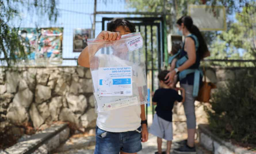 A girl in Jerusalem holds up a Covid test kit amid a nationwide testing campaign before Israeli schools open.