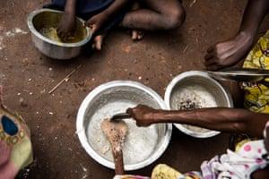 People eat at the Katanika displacement settlement