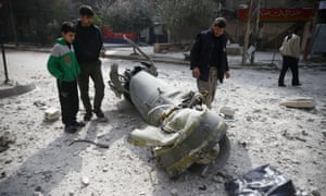 People inspect the remains of a missile in the town of Douma in eastern Ghouta, Syria