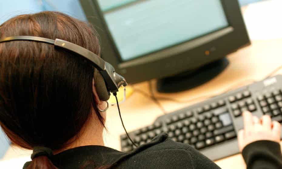 A woman in a telephone headset at a call centre.