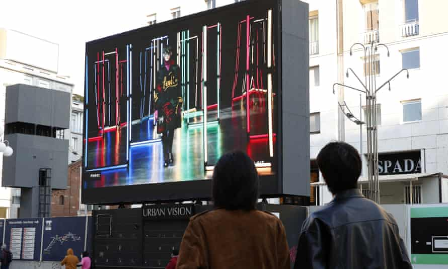 People in a street in Milan watching Fendi's energetic menswear show during the digital only fashion week in Italy.
