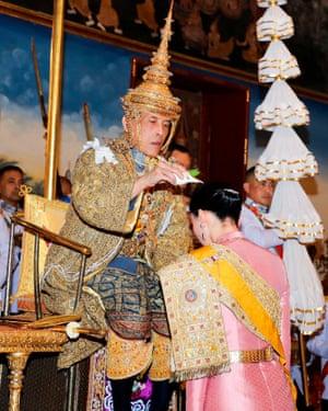 King Maha Vajiralongkorn and Queen Suthida perform a ritual during his coronation in Bangkok.