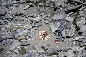 Ponte Brolla, Switzerland: A man sunbathes surrounded by rocks in the Maggia river