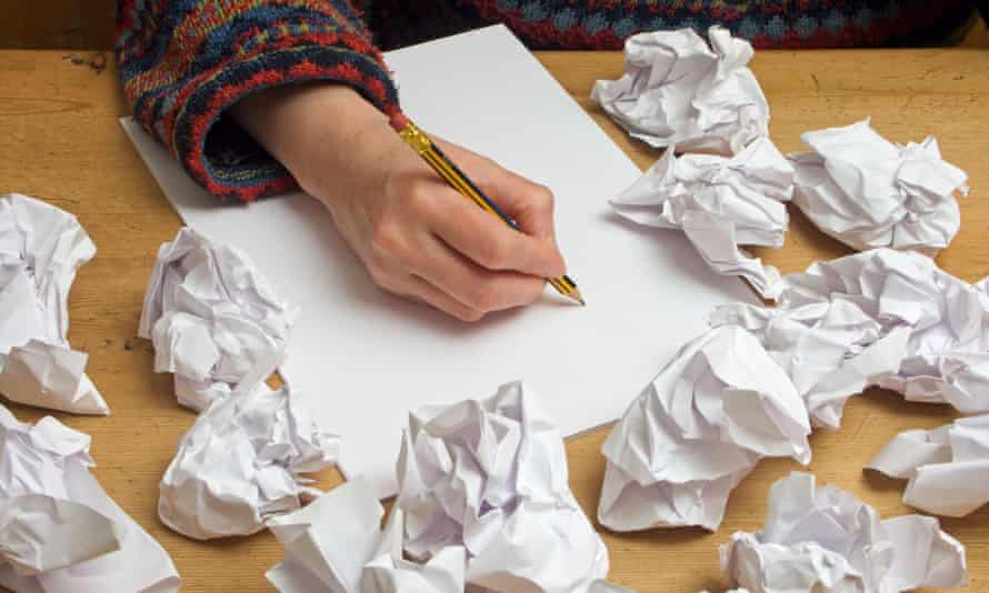 Someone with writers block trying to write on a blank sheet of paper surrounded by previous rejected attempts. Image shot 2006. Exact date unknown.A6MPXC Someone with writers block trying to write on a blank sheet of paper surrounded by previous rejected attempts. Image shot 2006. Exact date unknown.