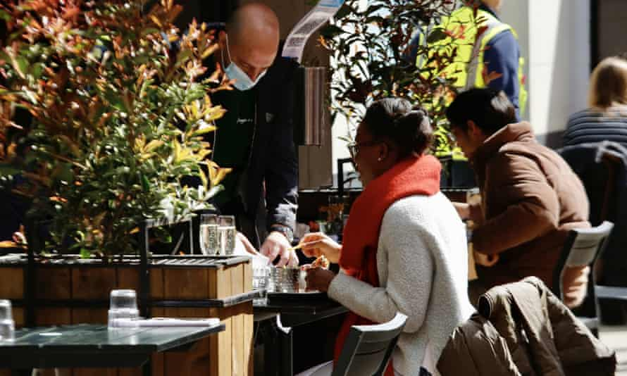A waiter talking to a woman at an outside table of a cafe or restaurant flanked with tubs of plants